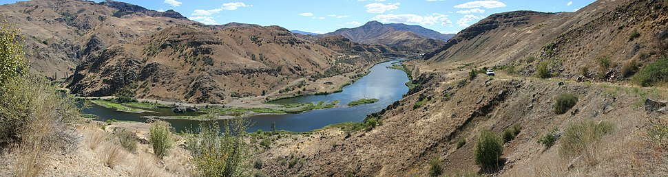 The Snake River bends through Hells Canyon on the Idaho–Oregon border, looking towards Idaho, with the Oxbow Dam in the background.