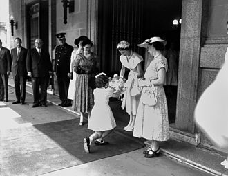 Curtsy - A young girl presenting flowers to Queen Elizabeth II outside Brisbane City Hall in March, 1954.