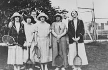 Five women standing with tennis rackets in hand