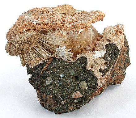 A combination specimen of four zeolite species. The radiating natrolite crystals are protected in a pocket with associated stilbite. The matrix around and above the pocket is lined with small, pink-colored laumontite crystals. Heulandite is also present as a crystal cluster on the backside Stilbite-Ca-Natrolite-Laumontite-247898.jpg