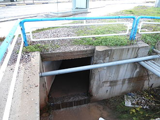 Storm drain - A storm drain culvert under the main road empties into a bigger open channel
