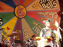 Stevens performing in front of a large song wheel