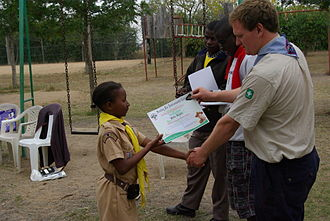 Kenya Scouts Association - A Kenyan Sungura Scout receiving their badge and certificate during an Award Ceremony at the end of a camp.