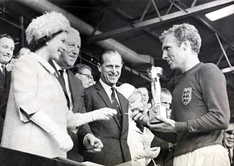 Queen Elizabeth II presenting the Jules Rimet trophy to 1966 World Cup winning England captain Bobby Moore The Queen presents the 1966 World Cup to England Captain, Bobby Moore. (7936243534).jpg
