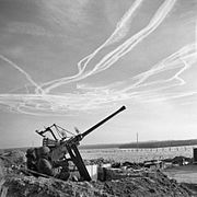 The crew of a Bofors anti-aircraft gun view vapour trails in the sky high above the Dutch-German border near Brunssum, 25 December 1944. B13136
