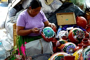 Handcrafts and folk art in Michoacán - Woman painting pot at the Palm Sunday Handcraft Market in Uruapan