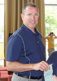 Tom Fitzgerald wearing a blue polo, looking directly at the camera and smiling