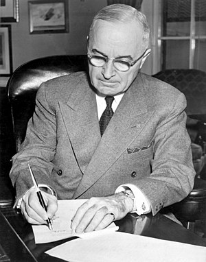 President Harry S. Truman is shown at his desk...