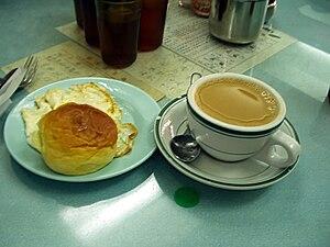 Hong Kong-style milk tea - Hot milk tea in a coffee cup accompanies a breakfast