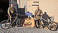 U.S. Air Force Tech. Sgt. Juan Sanchezduarte, right, and Senior Airman Mark Zorich, both assigned to the 451st Expeditionary Logistics Readiness Squadron, pose in front of a bike repair shop at Camp Losano 131111-F-BY961-011.jpg