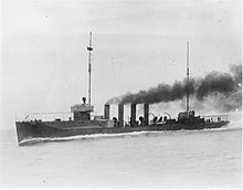 A black and white photo of the warship.  Shown in motion with black smoke billowing from its four smokestacks, the ship has two masts but no sails.
