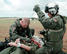 Color photograph of a United States Navy hospital corpsman listening for correct placement of an endotracheal tube in a simulated trauma victim during a search and rescue exercise. His assistant is holding a bag of intravenous fluid.
