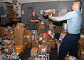 US Navy 030305-N-1512S-070 LCpl Adam Hadjis passes Postal Clerk 3rd Class Brian Etcheson a package while sorting in coming mail in the Lower Vehicle Stowage aboard the amphibious assault ship USS Kearsarge.jpg