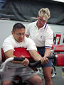 US Navy 030617-N-1929W-001 Sharkie Stielper (right), Civilian Afloat Program Manager for Navy Morale , Welfare and Recreation (MWR), explains proper technique on a bicep curl to Yeoman 1st Class Juan Gonzales, from San Antonio.jpg