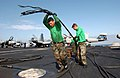 US Navy 040331-N-6213R-333 Airman Manuel Santis, of Chicago, Ill., pulls away an arresting cable after being replaced on the flight deck aboard the nuclear powered aircraft carrier USS John C. Stennis (CVN 74) during a schedule.jpg