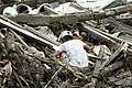 US Navy 050110-M-0678H-005 An Indonesian man looks through debris around his home for his personal effects in the city of Meulaboh.jpg