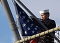 US Navy 050325-N-2970T-004 Storekeeper 3rd Class Jenovitz Danscel, assigned to the amphibious dock landing ship USS Fort McHenry (LSD 43) prepares to hoist the American Flag during morning colors.jpg