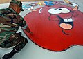 US Navy 050401-N-3019M-001 Boatswain's Mate 2nd Class Ricardo Valverde, assigned to Mobile Diving Salvage Unit One (MDSU-1), inspects a sidewalk graphic design he painted for children at Waipahu Elementary School.jpg