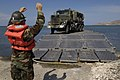US Navy 050509-N-3642E-013 A Sailor assigned to the amphibious transport dock ship USS Austin (LPD 4) guides a five-ton truck from the Puerto Rican National Guard's 699th Engineering Company onto a causeway.jpg