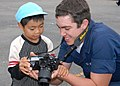 US Navy 071101-N-4649C-104 Mass Communication Specialist Seaman Apprentice Trevor Welsh, a Sailor assigned to submarine tender USS Frank Cable (AS 40), shows photographs to a child at the Shunko Gakuen orphanage.jpg