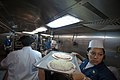 US Navy 100626-N-5319A-009 Chief Fire Controlman Guadalupe Galindo carries a tray of pizzas to the ovens as the Navy and Marine Corps senior enlisted aboard the amphibious transport dock ship USS New Orleans (LPD 18).jpg