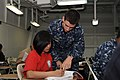 US Navy 110728-N-UE944-014 Ensign Ramon Vazquez assists Seaman Maan Palad during the ship's Armed Services Vocational Aptitude Battery (ASVAB) Acad.jpg