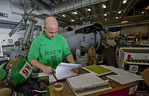US Navy 111231-N-OY799-223 Aviation Structural Mechanic 1st Class Steve Lind reviews maintenance sheets for an MH-60S Sea Hawk helicopter from the.jpg