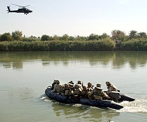 An Apache attack helicopter provides close air support to United States Army soldiers patrolling the Tigris River southeast of Baghdad, Iraq during the Iraq War.