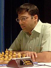 A photograph of a man playing Chess with white set.