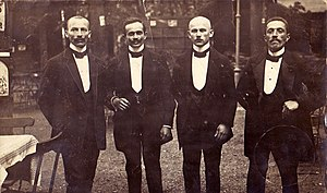 "Gratuity - The first usage of the term ""tip"" in the sense of giving a gratuity dates back to 1706 (pictured here are European waiters from the early 1900s)"