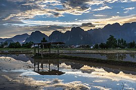 Water reflection of a wooden hut with colorful sky and karst mountains in a paddy field at sunset Vang Vieng Laos.jpg