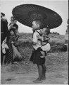 While big brother's attention is riveted on some object up the road on Okinawa, the little fellow protests against... - NARA - 532378.tif