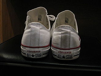 Chuck Taylor All-Stars - A pair of white low-cut All Star sneakers, showing the current back heel logo