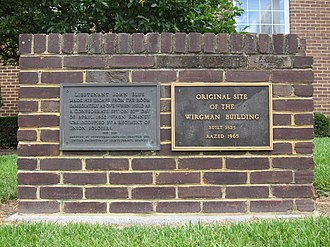 """Wirgman Building - Two historical markers in front of the Bank of Romney memorialize the Wirgman Building: the first marker (pictured left) was erected by the United Daughters of the Confederacy to commemorate Lieutenant John Blue's escape from the building during the American Civil War, and the second marker (pictured right) reads """"Original Site of the Wirgman Building. Built 1825. Razed 1965."""""""