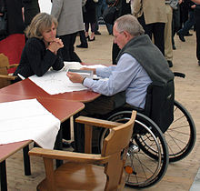 Schäuble sits in his wheelchair at a table facing his wife, dressed casually during what was a ten-hour performance of Schiller's Wallenstein trilogy