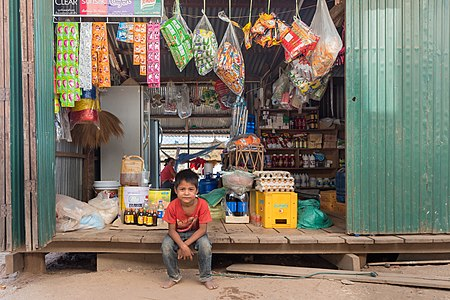 Young vendor sitting in a grocery store in Don Som, Si Phan Don, Laos