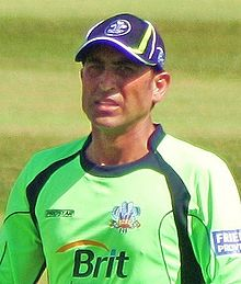 A man in parrot-green shirt and blue cap standing in a cricket ground