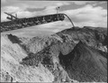 """""""The 175-foot boom of the conveyor stacker section discharging material from the east side, 7,000 feet distant."""" - NARA - 294006.tif"""