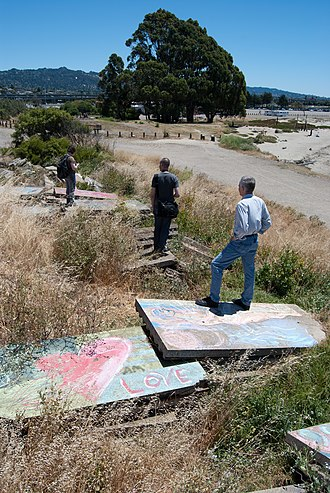 Albany Bulb - Hikers walk on concrete slabs next to the path, looking back towards the mainland.