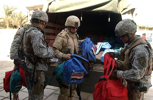 Reserve psychological operations soldiers hand out school supplies for Iraqi children. 301st PSYOP Company, USAR, Calif., and 3-7 Cavalry, Fort Stewart, Ga., soldiers give away school supplies in Safia Bint Abdul Mutaleb School in 2007.JPG