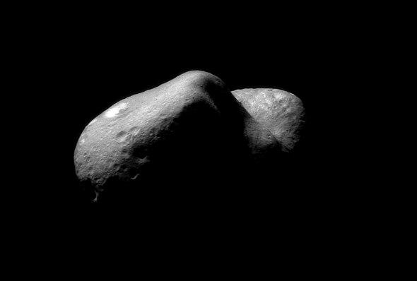 Questa immagine di Eros, presa il 14 febbraio 2000 dalla sonda NEAR (in realtà un mosaico composto da due immagini), i più piccoli dettagli distinguibili sono grandi circa 35 metri. Si riconoscono massi della dimensione di case in molti posti. Uno si trova sull'orlo del cratere gigante che separa le due metà dell'asteroide. Un'area luminosa è visibile nella parte superiore sinistra, e dei solchi possono essere visti subito sotto di essa. I solchi scorrono paralleli alla dimensione maggiore dell'asteroide.