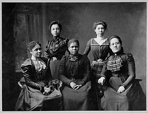 Black and white photograph of five women seated together