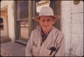 AN ELDERLY RESIDENT IN FRONT OF THE FEEDSTORE IN LEAKEY TEXAS, NEAR SAN ANTONIO - NARA - 554845.tif