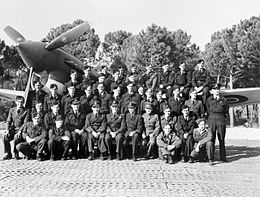 A group of uniformed men posing in front of a single-engined fighter plane