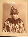 A Maori girl, Horonyairu, poses against a plain background. She has short hair decorated with feathers and facial tattoos around (a3c30aae-84fd-4583-b6e3-f1debc8ad219).JPG