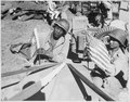 A U.S. Army soldier and a Chinese soldier place the flag of their ally on the front of their jeep just before the first... - NARA - 535573.tif