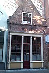 foto van Huis met gepleisterde topgevel; ontpleisterde top met vlechtingen op bakstenen tandlijst. Houten pui tot middendeur