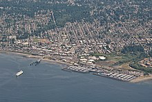An aerial picture of Downtown Edmonds, showing a city laid out in a grid of streets and buildings. The water takes up the bottom half of the picture, with a ferry approaching the dock.