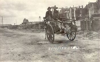 Two men in sombreros riding in a donkey-cart with a line of feet sticking out the back. They are riding down a dirt street away from the camera, with a line of buildings on the right.  Dated 15 May 1911.