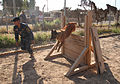 An Iraqi police officer with a major terrorism K-9 unit guides his dog over an obstacle during training at Contingency Operating Site Diamondback, in Mosul, Ninevah province, Iraq, May 23, 2011 110523-A-RH393-122.jpg